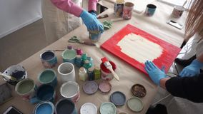 The artist prepares a picture. Red paint. Art Studio. Collaboration. Master Class. Artistic education. Paint cans on the table. Top view stock video