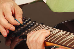 Artist put fingers for chords on electric guitar close up Royalty Free Stock Photos