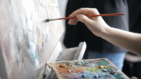 The artist puts brush to the palette of paints on an easel stock video