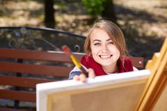 The female artist is painting a picture in the autumn park. Royalty Free Stock Image