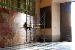 Artist repairing old painting Royalty Free Stock Photo