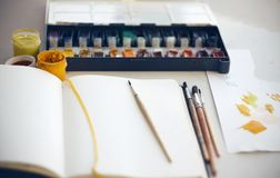 The artist`s Desk on which sketchbook, brushes, watercolor and gouache paints stock photo