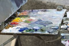 Artist`s easel with a palette of bright colors. Plastic bokeh royalty free stock photo