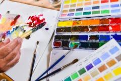 Artist's hand applying paint gouache Stock Photo