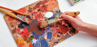 Artist's hand with brushes and palette of colors. The artist paints a picture of a paint brush in his hand with a palette closeup Royalty Free Stock Image