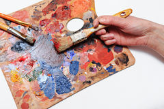 Artist's hand with brushes and palette of colors. The artist paints a picture of a paint brush in his hand with a palette closeup Royalty Free Stock Photos