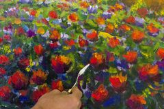 Art creative process. Artist create heart painting on canvas. Artist`s hand close-up paint Field of red poppies with palette knife impasto art landscape painting royalty free stock photography