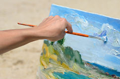 The artist's hand holding a brush, painting the picture Stock Images