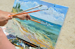 The artist's hand holding a brush, painting the picture Stock Photo