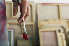 Artist's Hand Holding Paintbrush. Closeup of an artist holding paintbrush stock photography