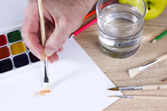 Artist`s hand at work, paints, brushes and pencils Royalty Free Stock Images