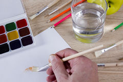 Artist`s hand at work, paints, brushes and pencils Stock Photography