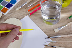 Artist`s hand at work, paints, brushes and pencils Stock Photos