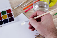 Artist`s hand at work, paints, brushes and pencils Royalty Free Stock Photo