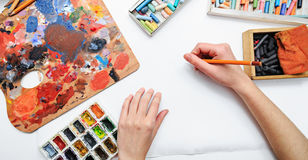 Artist's hand at work, paints, brushes and pencils Stock Photography