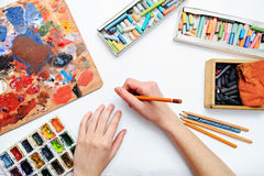 Artist's hand at work, paints, brushes and pencils Royalty Free Stock Images
