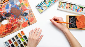 Artist's hand at work, paints, brushes and pencils Royalty Free Stock Photography