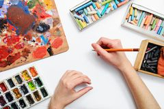 Artist's hand at work, paints, brushes and pencils Royalty Free Stock Photo