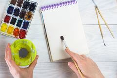 The artist`s hands, paint palette brushes, different colors. The girl is drawing. The artist`s tools for real art and inspiratio stock photography