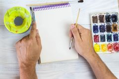 The artist`s hands, paint palette brushes, different colors. The man is drawing. The artist`s tools for real art and inspiration royalty free stock photo