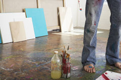 Artist's Legs By Brushes And Paint Thinner In Studio Royalty Free Stock Image