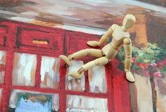 Artist Manikin on Painting. Artist`s manikin sitting on a painting Stock Photo