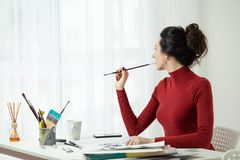 Artist`s model. girl in red clothes is sitting in the office. Artist`s workplace, one young woman only, mascara brush. the girl draws on canvas. artist`s Royalty Free Stock Image