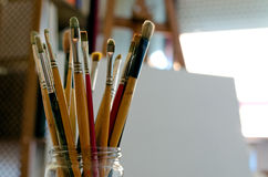 Artist's Paintbrushes. A large jar is filled with paintbrushes inside an artist's studio Stock Photo