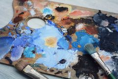 Artist`s palette with colorful oil paint strokes and paintbrushe stock photography