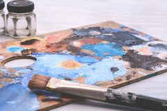 Artist`s palette with colorful oil paint strokes and paintbrushe stock images
