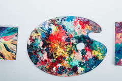 The artist`s palette stained with paint. On a white background, nobody.  Stock Photography