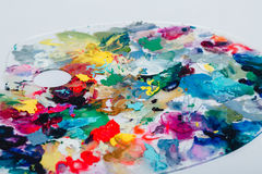 The artist`s palette stained with paint. On a white background, nobody.  Stock Photo
