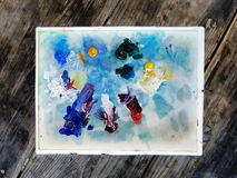 Artist`s Pallet On A Wooden Table. A white pallet, covered with smudges of oil paint. Mostly blues, but with some red and yellow stock image