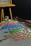 Artist's painting  palette and workspace. Artist's studio interior workspace showing palette with premixed oil paint colors in various shades and nuances Stock Image