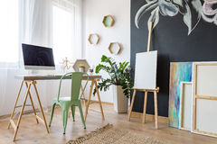 Artist`s study room. With desk with computer and paintings by the black wall stock image