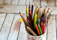 Artist's tool. Colored pencils in vibrant colors, well sharpened in vase on a wooden table Stock Photo