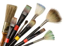 Artist's used brushes. A bunch of used paintbrushes over pure white background stock photos