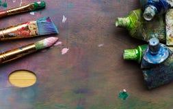 Artist& x27; s warsztat Sztaluga z muśnięciami i tubkami farba Obrazy Stock