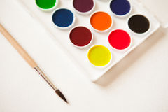 Artist's work space. Set of watercolor paints in white base, brush on sheet of white watercolor paper. Artistic background Royalty Free Stock Image
