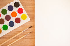 Artist's work space. Set of watercolor paints in white base, sheet of white watercolor paper, 2 brushes on light woden background. Artistic background Royalty Free Stock Images