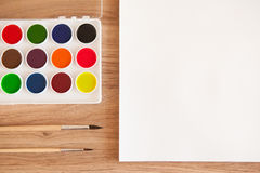 Artist's work space. Set of watercolor paints in white base, sheet of white watercolor paper, 2 brushes on light woden background. Artistic background Royalty Free Stock Photography