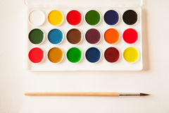 Artist's work space. Set of watercolor paints in white base, sheets of white watercolor paper, brush on light woden background. Artistic background Royalty Free Stock Photography