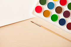 Artist's work space. Set of watercolor paints in white base, sheets of white watercolor paper, brush on light woden background. Artistic background Stock Photography