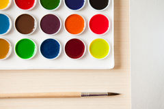 Artist's work space. Set of watercolor paints in white base, sheets of white watercolor paper, brush on light woden background. Artistic background Royalty Free Stock Images