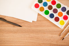 Artist's work space. Artist's workspace. Set of 18 watercolor paints in white base, 2 sheets of white watercolor paper, 2 brushes, pen on light woden background Royalty Free Stock Photography