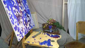 The artist`s workplace, canvas standing on a wooden easel, around scattered brushes, tubes of paint and flowers. The artist`s workplace, canvas in oil paints stock video footage