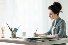 Artist`s model. girl painter working in the office. Artist`s workplace, one young woman only, mascara brush. the girl draws on canvas. artist`s workplace Stock Photo