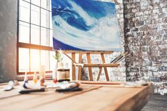 Artist`s workplace in the studio. Painting on canvas on the easel in the studio. Artist workshop. Lens flare effect Stock Photos