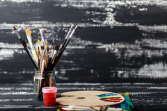 Artist`s workshop. Canvas, paint, brushes, palette knife lying on the table.Art tools.Artist workplace background.Acrylic paint an. D brushes.Art picture with stock photos