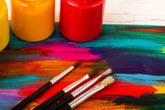 Artist`s workshop. Canvas, paint, brushes, palette knife lying on the table.Art tools.Artist workplace background.Acrylic paint an. D brushes.Art picture with royalty free stock image
